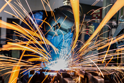 welder at work with sparks flying