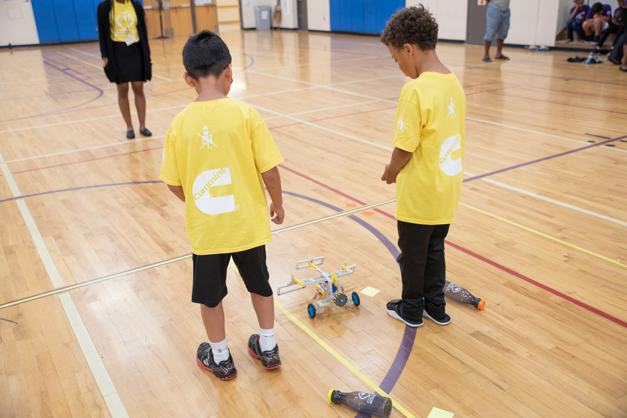 Two SEEK third grade youth begin to send their robot through the obstacle course.