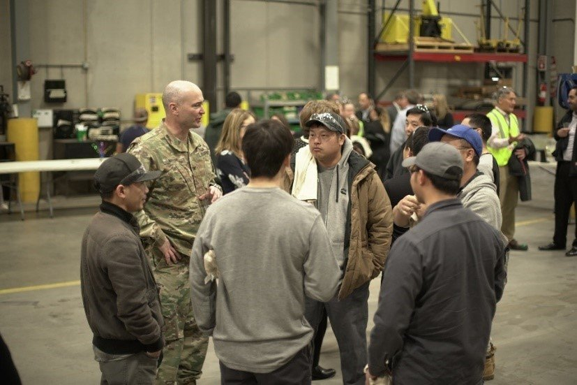 Colonel Adrian Marsh of the Department of Defense engages with Cummins employees who have worked on the AMMPS units.