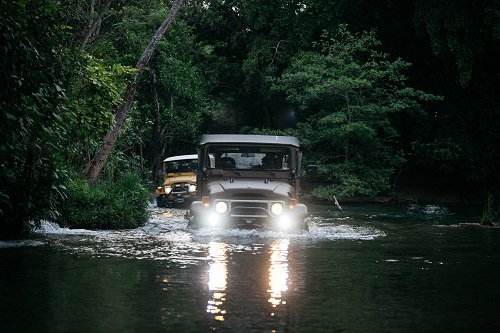 The Clean Cruisers wade through a stream in Central America