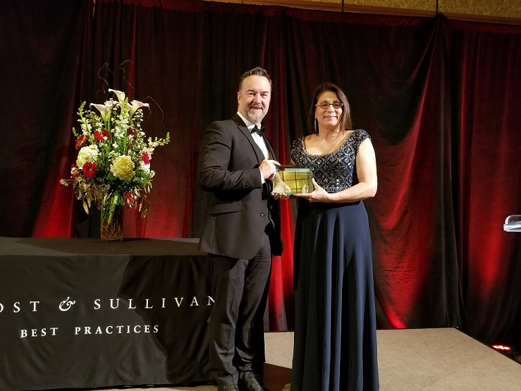 Cummins' Frank Friesacher, Executive Director of Product Commercialization, and Paula P. Watson, Director – Customer Success and Digital Solutions Integration, accept the Frost & Sullivan award.