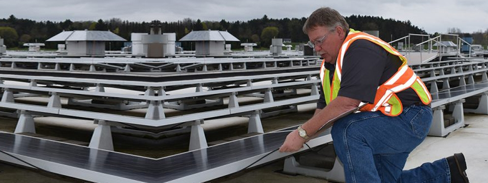 electrician inspects connections at Cummins solar array