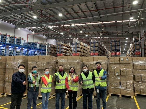 Cummins employees in Shanghai stand in front of one of the shipments of masks.