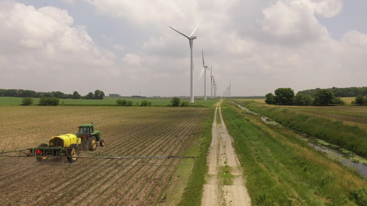 A farmer works in a field within the Meadow Lake Wind Farm expansion earlier this year. Cummins helped the wind farm expand in 2018.