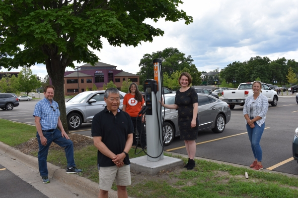 Team members gather around the new electric vehicle charging station developed in the city of Shoreview, Minnesota. Cummins employees contributed to the effort and are now working to create a charging station in the city of White Bear Lake (photo courtesy of the Great Plains Institute).