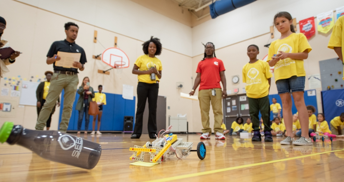 SEEK third grader controls her team's robot through the obstacle course, as Cummins employees, SEEK mentors and others watch in amazement.