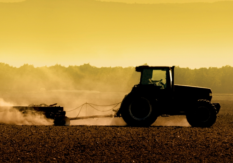 tractor working a field at sunset