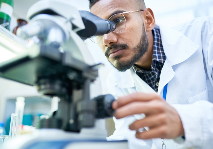 scientist looking at samples through a microscope