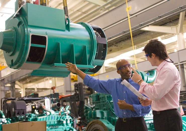 cummins employees talking in the manufacturing plant