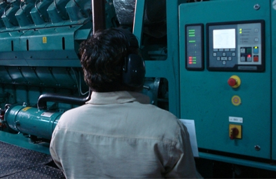 indian worker inspecting cummins generator